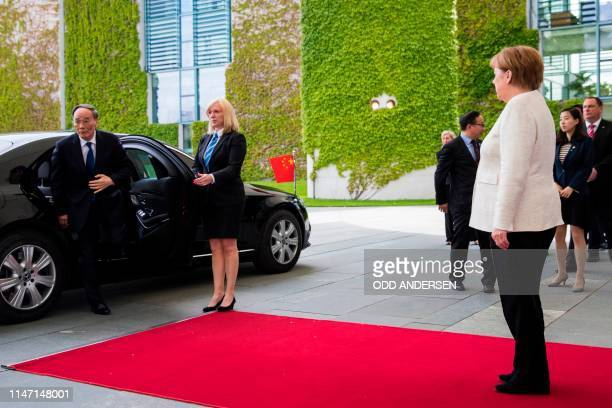 German Chancellor Angela Merkel greets Chinese Vice President Wang Qishan on his arrival prior to a meeting at the Chancellery in Berlin on May 31...