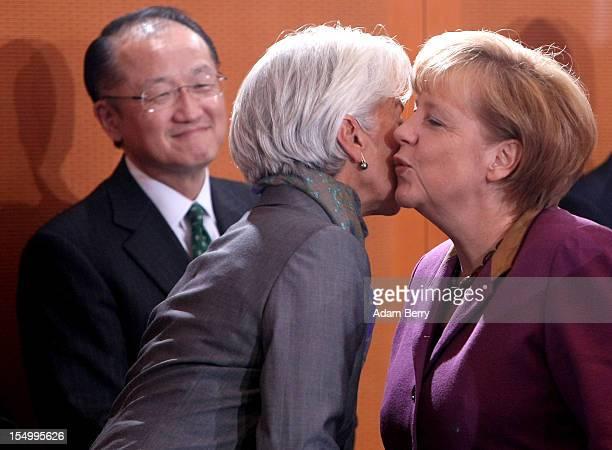 German Chancellor Angela Merkel greets Christine Lagarde managing director of the International Monetary Fund as Jim Yong Kim president of the World...