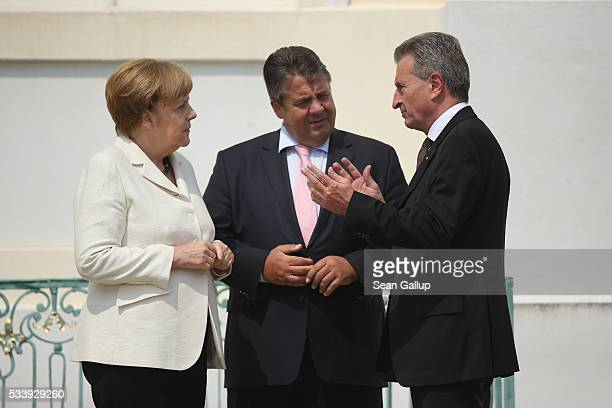 German Chancellor Angela Merkel greets European Commissioner for Digital Economy and Society Guenther Oettinger as Vice Chancellor and Economy and...
