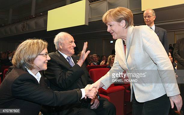 German chancellor Angela Merkel greets former chancellor Helmut Kohl sitting on his wheelchair and his wife Maike KohlRichter before the start of an...