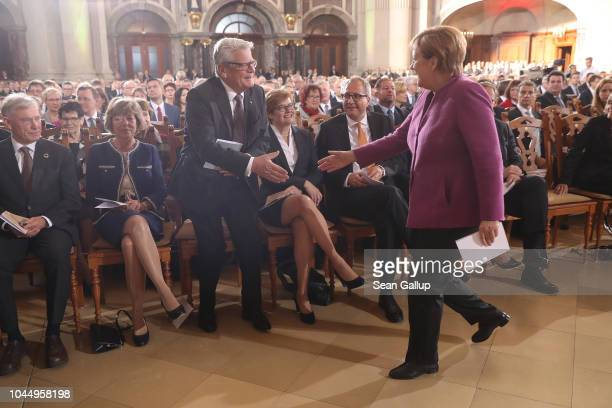 German Chancellor Angela Merkel greets former German President Joachim Gauck as formrer President Horst Koehler looks on prior to a religious service...