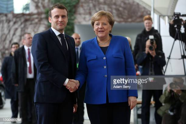 German Chancellor Angela Merkel greets French President Emmanuel Macron as he arrives for an international summit on securing peace in Libya at the...