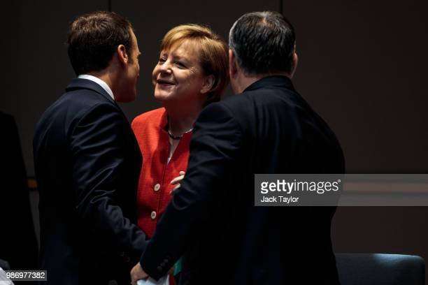 German Chancellor Angela Merkel greets French President Emmanuel Macron ahead of roundtable discussions on the final day of the European Council...