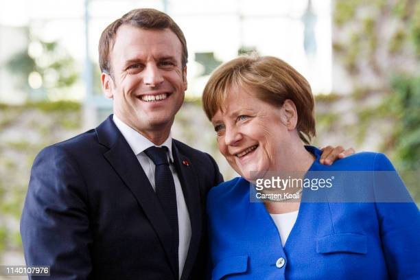 German Chancellor Angela Merkel greets French President Emmanuel Macron upon his arrival at the Chancellery for the Western Balkans Conference on...
