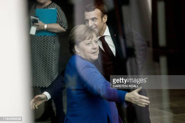 German Chancellor Angela Merkel greets French President Emmanuel Macron upon his arrival to attend the Peace summit on Libya at the Chancellery in...