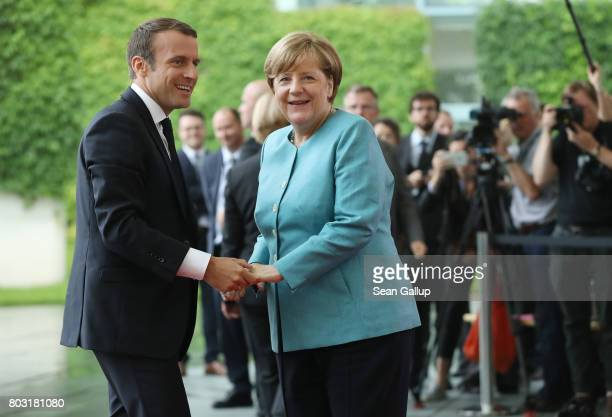 German Chancellor Angela Merkel greets French President Emmanuel Macron prior to a meeting of European Union leaders at the Chancellery on June 29...