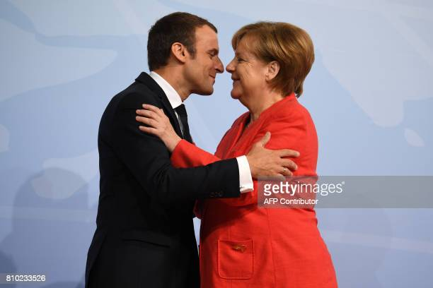 German Chancellor Angela Merkel greets French President Emmanuel Macron prior to the start of the first working session of the G20 meeting in Hamburg...