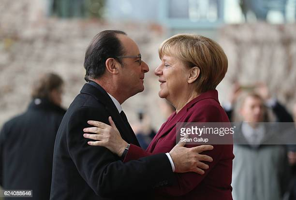 German Chancellor Angela Merkel greets French President Francois Hollande upon his arrival for talks between US President Barack Obama and western...