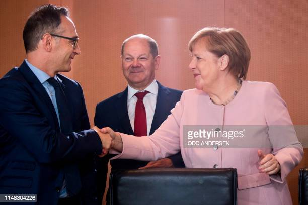 German Chancellor Angela Merkel greets German Foreign Minister Heiko Maas and German Finance Minister and ViceChancellor Olaf Scholz during the...