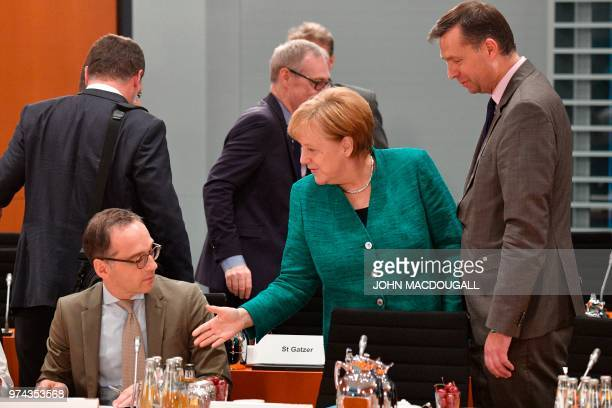 German Chancellor Angela Merkel greets German Foreign Minister Heiko Maas as German State minister Stephan Mayer watches on June 14 2018 at the...