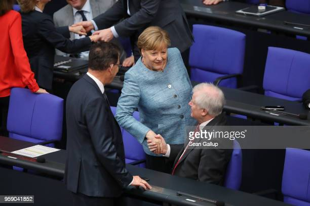 German Chancellor Angela Merkel greets Interior Minister Horst Seehofer as she arrives for debates at the Bundestag over the federal budget on May 16...
