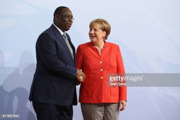 German Chancellor Angela Merkel greets Senegal Presidentt Macky Sall upon his arrival for the first day of the G20 economic summit on July 7 2017 in...