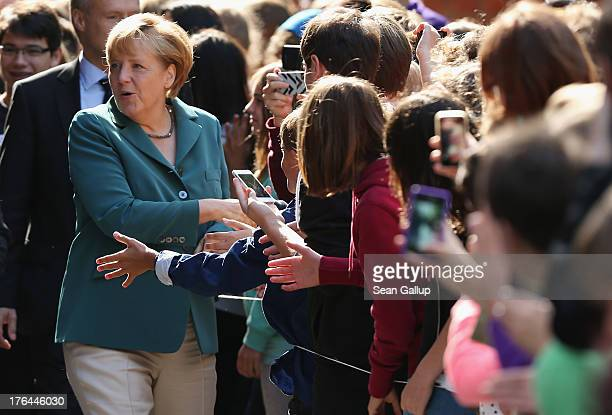 German Chancellor Angela Merkel greets students upon her arrival at the HeinrichSchliemannGymnasium high school on August 13 2013 in Berlin Germany...