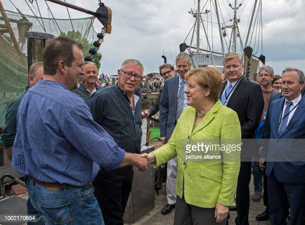 German Chancellor Angela Merkel greets the crab cutter captain Fritz Dirks in Neuharlingersiel Germany 14 July 2017 Speaker of the German coastal...
