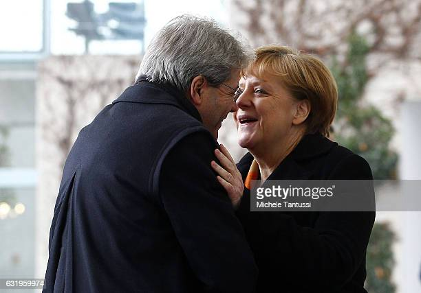 German Chancellor Angela Merkel greets the new Italian Prime Minister Paolo Gentiloni before they review a guard of honor upon Gentilon's arrival at...
