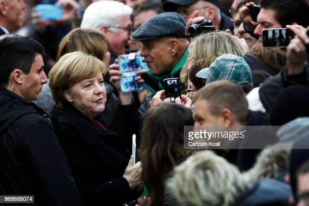 German Chancellor Angela Merkel greets the visitors following a service in Schlosskirche church to commemorate the 500th anniversary of Luther's...