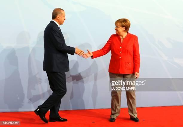 German Chancellor Angela Merkel greets Turkey's President Recep Tayyip Erdogan at the start of the G20 meeting in Hamburg, northern Germany, on July...