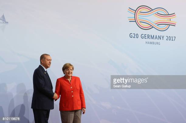 German Chancellor Angela Merkel greets Turkish President Recep Tayyip Erdogan upon his arrival for the first day of the G20 economic summit on July 7...