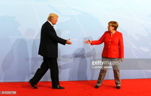 German Chancellor Angela Merkel greets US President Donald Trump at the start of the G20 meeting in Hamburg, northern Germany, on July 7. - Leaders...
