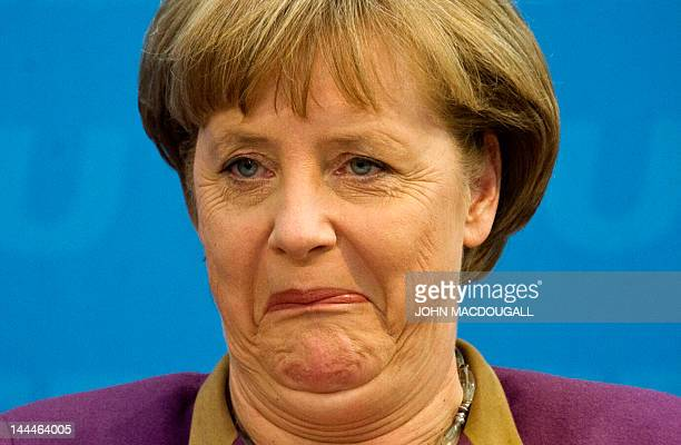 German Chancellor Angela Merkel grimaces as she addresses a press conference following a poor showing by her Christian Democratic Party in regional...
