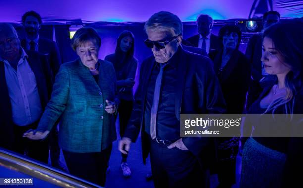 German Chancellor Angela Merkel guides supporters of her party including singer Heino and model Cathy Hummels through the CDU's #fedidwgugl Haus a...