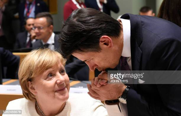 TOPSHOT German Chancellor Angela Merkel has her hand kissed by Italy's Prime Minister Giuseppe Conte ahead of an Asia Europe Meeting at the European...