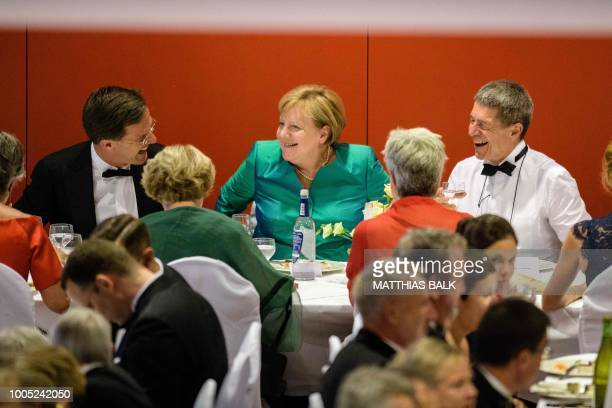 German Chancellor Angela Merkel her husband Joachim Sauer and Dutch Prime Minister Mark Rutte share a laugh during a break in the show at the opening...