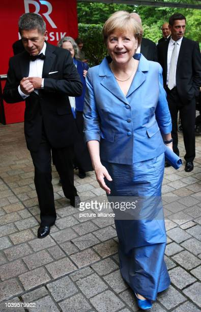 German Chancellor Angela Merkel her husband Joachim Sauer and his son Daniel Sauer arrive for the Wagner opera 'Siegfried' at the Bayreuth Festival...
