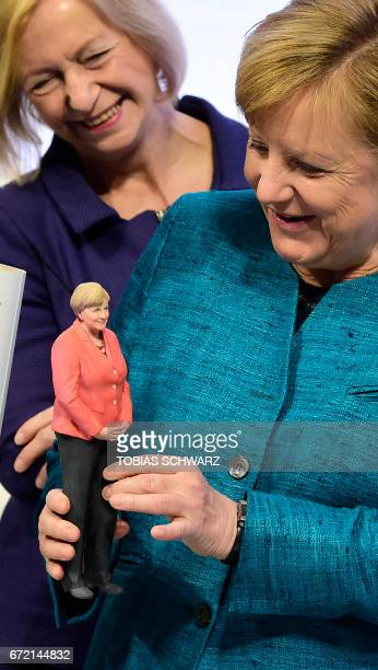 German Chancellor Angela Merkel holds a 3D printed figurine featuring herself she was given by the chairman of Siemens as German Education and...