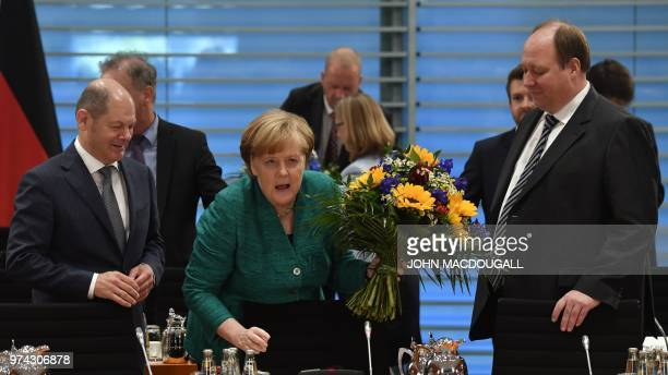German Chancellor Angela Merkel holds a bouquet before offering it to German Finance Minister and ViceChancellor Olaf Scholz for his birthday as...