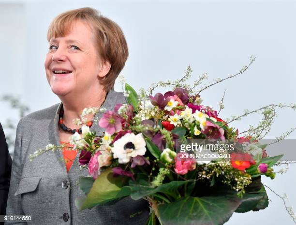 German Chancellor Angela Merkel holds a flower bouquet given to her by the President of the German Horticultural Association in the chancellery in...
