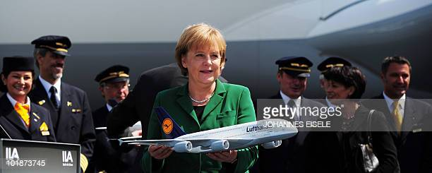 German Chancellor Angela Merkel holds a model of a Lufthansa Airbus A380 at the International Aerospace Exhibition on June 8 2010 at the Schoenefeld...