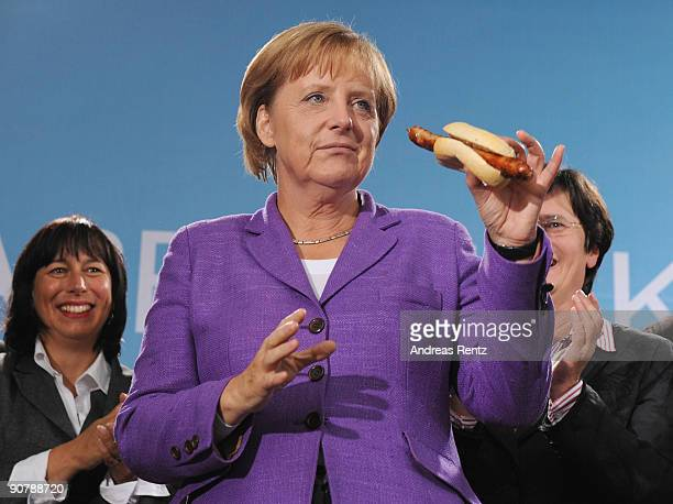 German Chancellor Angela Merkel holds a original grilled Thuringian sausage during an election rally on September 15 2009 in Erfurt Germany German...