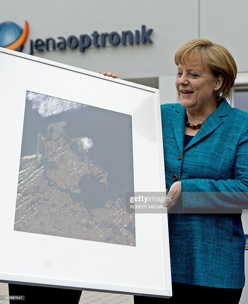 German Chancellor Angela Merkel holds a picture of Baltic Sea Island of Ruegen after a visit of the Jena-Optronik GmbH (Ltd), a German provider of opto-electronic instruments and sub-systems for space applications, on May 2 , 2013 in Jena, eastern Germany.