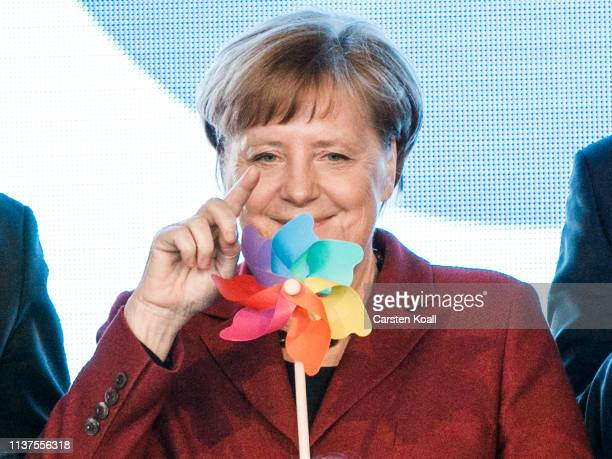 German Chancellor Angela Merkel holds a windmill as she attends the inauguration of the Arkona offshore wind park on Ruegen Island on April 16 2019...