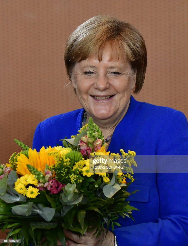 Weekly government cabinet meeting photos and images getty images german chancellor angela merkel holds flowers for her 64th birthday before the weekly cabinet meeting in izmirmasajfo