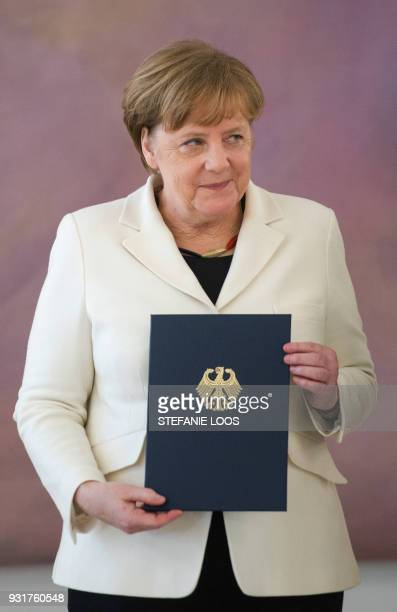 German Chancellor Angela Merkel holds her certificate of appointment she was given by the German President on March 14 2018 at Bellevue Palace in...