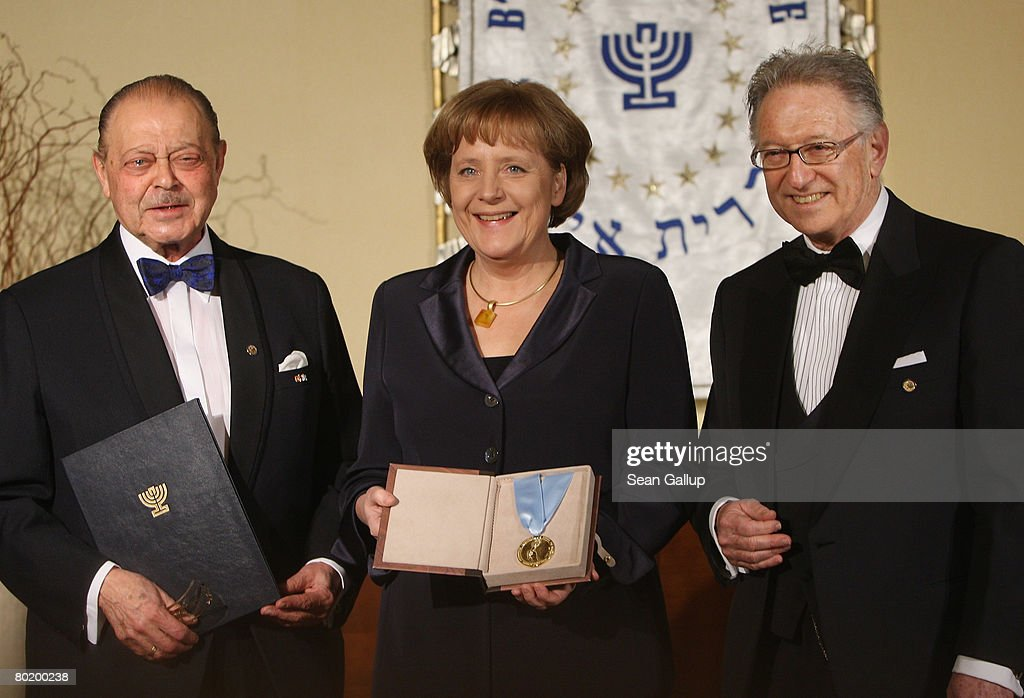 German Chancellor Angela Merkel holds her Gold Medal from B'nai B'rith while standing with B'nai B'rith Europe Honourary President Joseph Domberger (L) and B'nai B'rith Europe President Reinold Simon at the B'nai B'rith Europe Award of Merit at the Marriot hotel on March 11, 2008 in Berlin, Germany.