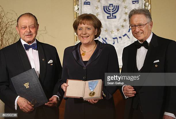 German Chancellor Angela Merkel holds her Gold Medal from B'nai B'rith while standing with B'nai B'rith Europe Honourary President Joseph Domberger...