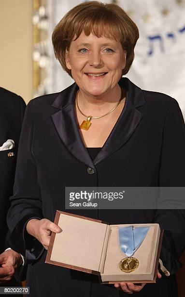 German Chancellor Angela Merkel holds her Gold Medal from B'nai B'rith at the B'nai B'rith Europe Award of Merit at the Marriot hotel on March 11...