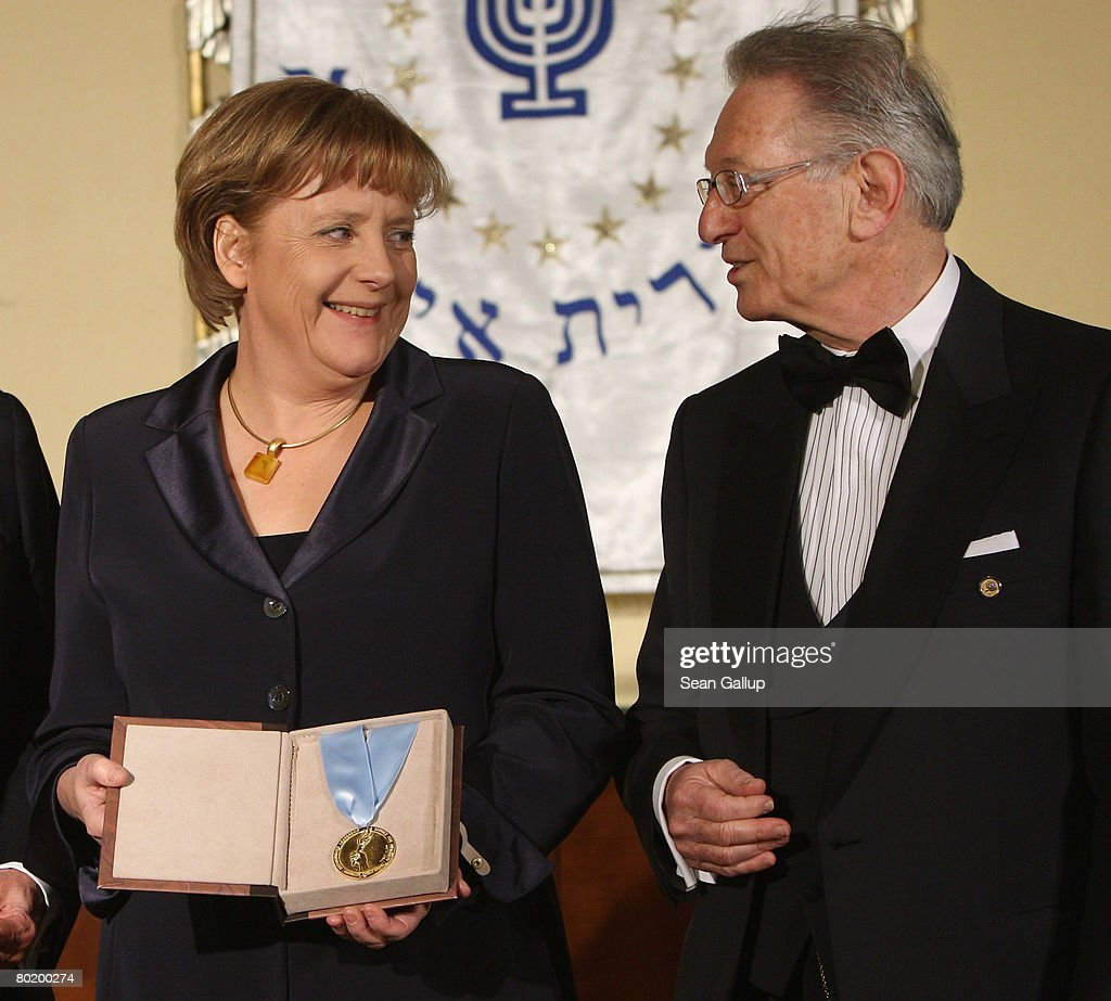German Chancellor Angela Merkel holds her Gold Medal from B'nai B'rith while standing with B'nai B'rith Europe President Reinold Simon at the B'nai B'rith Europe Award of Merit at the Marriot hotel on March 11, 2008 in Berlin, Germany.