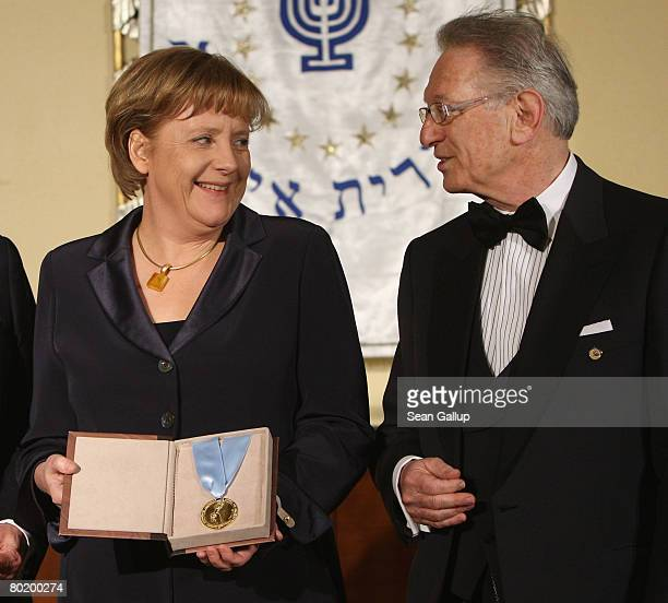 German Chancellor Angela Merkel holds her Gold Medal from B'nai B'rith while standing with B'nai B'rith Europe President Reinold Simon at the B'nai...
