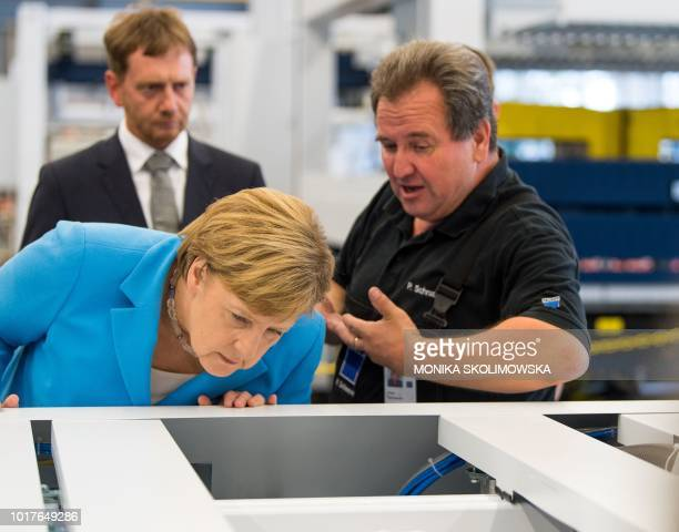 German Chancellor Angela Merkel inspects a machine as she visits the Trumpf Sachsen GmbH engineering company in Neukirch near Dresden eastern Germany...