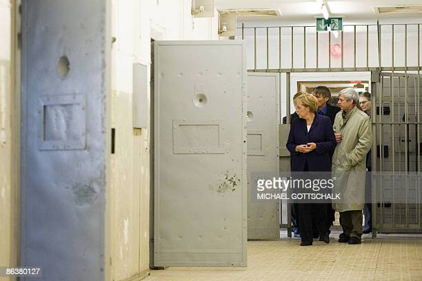 German Chancellor Angela Merkel inspects a prison cell with former prisoner Gilbert Furian as she visits the memorial site at the former Stasi East...