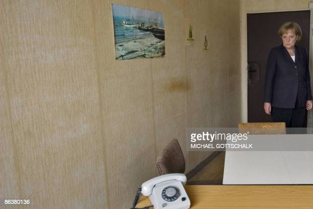 German Chancellor Angela Merkel inspects a prison office as she visits the memorial site at the former Stasi East German secret police prison in...