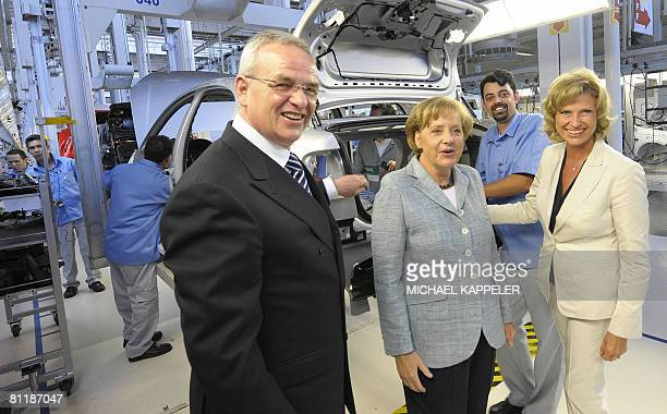 German Chancellor Angela Merkel inspects the production of a Volkswagen car during a visit to the VW plant accompanied by Volkswagen CEO Martin...