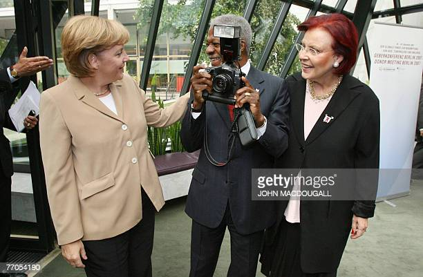 German Chancellor Angela Merkel interrupts former UN secretary general Kofi Annan as he was taking pictures of press photographers, upon her arrival...
