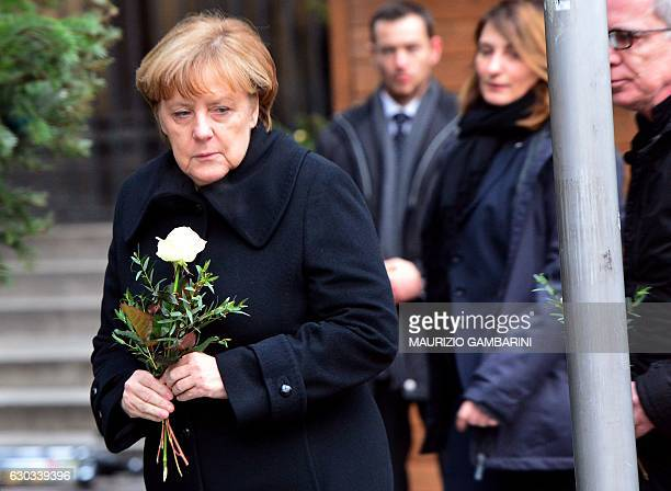German Chancellor Angela Merkel is about to lay flowers with German Interior Minister Thomas de Maiziere on December 20 2016 at the site where a...