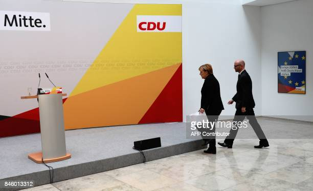 German Chancellor Angela Merkel is accompanied by CDU secretary general Peter Tauber as she arrives to give a statement on September 12 2017 in...
