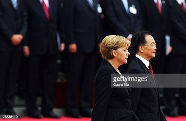 German Chancellor Angela Merkel is accompanied by Chinese Premier Wen Jiabao as they view an honour guard during a welcoming ceremony outside the...